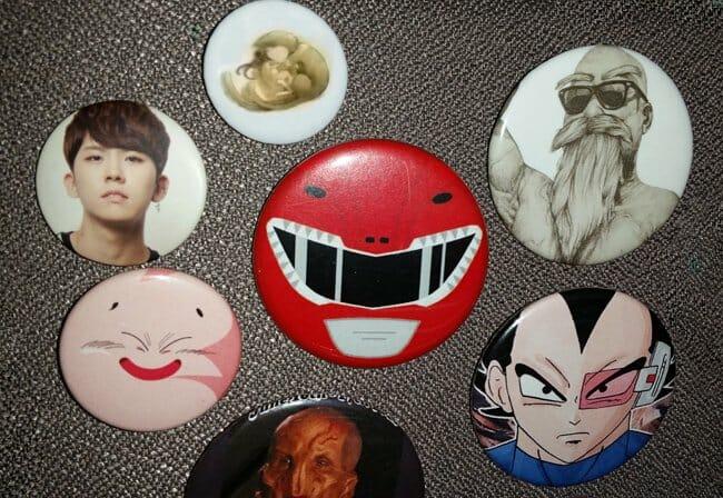 Pinback buttons of: K-Pop man, cat, Fat Buu, Saru, Red Power Ranger, Master Roshi, Vegeta